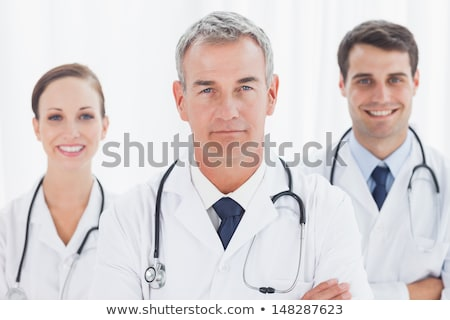 smiling matured doctor posing with folded arms stock photo © stockyimages