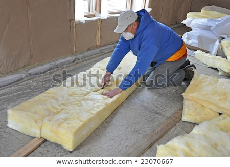 man cutting insulation material for building stock photo © kzenon