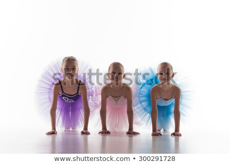 Stock photo: Three little ballet girls sitting in tutus and posing together