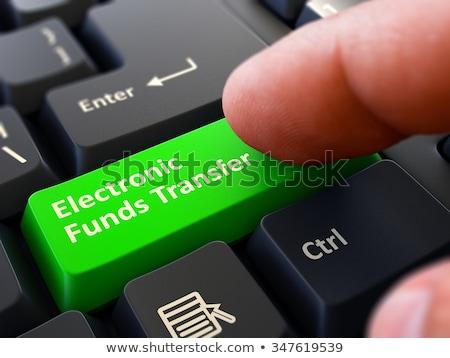 pressing green button electronic funds transfer on black keyboar stock photo © tashatuvango