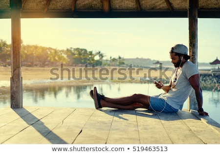 handsome black man resting on the beach stock photo © studiostoks