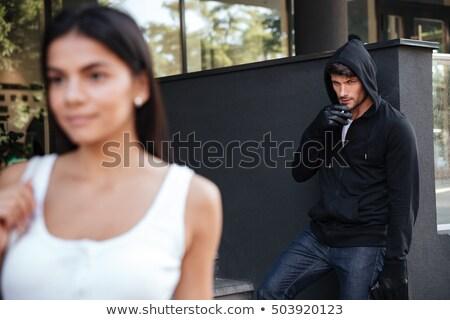Homem ladrão fumador olhando mulher caminhada Foto stock © deandrobot