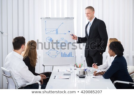 Businessman on the chair presenting graphs Stock photo © bluering