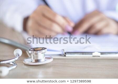 młodych · lekarz · piśmie · medycznych · sprawozdanie · odizolowany - zdjęcia stock © wavebreak_media