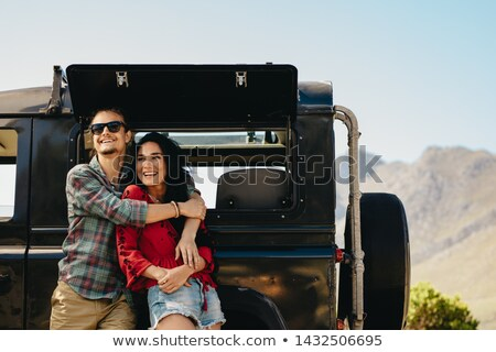 Couple embracing by an SUV smiling Stock photo © IS2