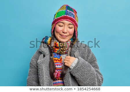 Image of two teenage women wearing hats and scarfs smiling at ca Stock photo © deandrobot