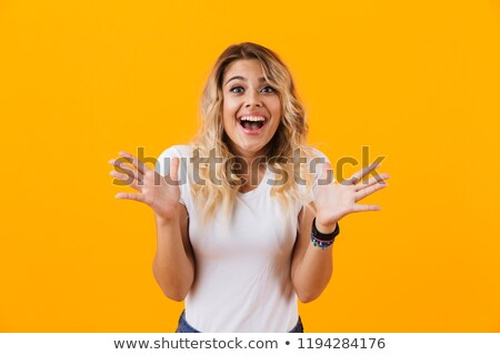 Photo of cheerful blond woman in basic clothing wondering and sm Stock photo © deandrobot