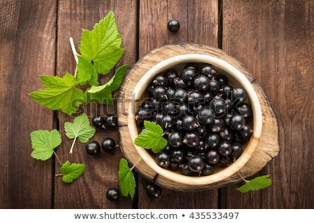 Stock photo: Blackcurrant berries with leaves, black currant in green bowls.