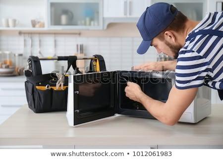 Foto stock: Man Repairing Microwave Oven