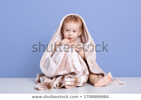 The boy on the beach wrapped in a towel, wet after swimming stock photo © galitskaya