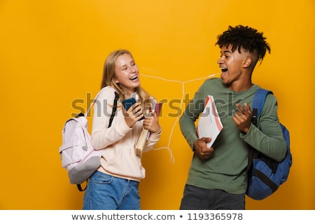 Photo of joyous students man and woman 16-18 wearing earphones u Stock photo © deandrobot