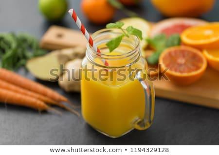 mason jar glass of fruit juice on slate table top stock photo © dolgachov