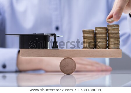 Graduation Hat And Stack Of Coins On Seesaw stock photo © AndreyPopov