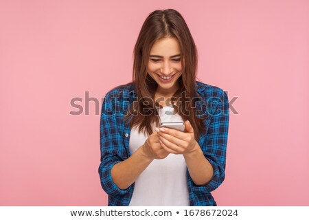 Happy young brunette female scrolling or reading message in smartphone outdoors Stock photo © pressmaster