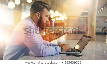 young businessman in blue shirt using smartphone and laptop and making notes stock photo © pressmaster