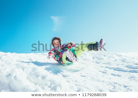 Kid Sliding With Sledge In The Snow Stock photo © AndreyPopov
