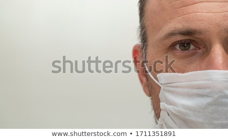 Pandemic coronavirus, Covid-19. Serious young man dressed in sweatshirt and jeans, wears respiratory Stock photo © vkstudio