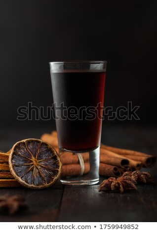 Shot glass of herb liqueur with cinnamon and dry oranges on dark wood background. Stock photo © DenisMArt