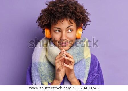 ストックフォト: Attractive Woman With Headphones Looking At Something While Standing Against A White Background
