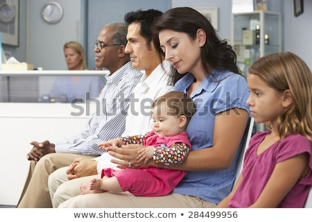 mother and daughter in the waiting room at doctors office stock photo © dacasdo