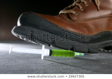 Boot treading a green liquid syringe Stock photo © lunamarina