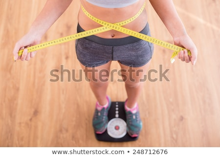 Woman standing on scale measuring waist with tape Stock photo © HASLOO