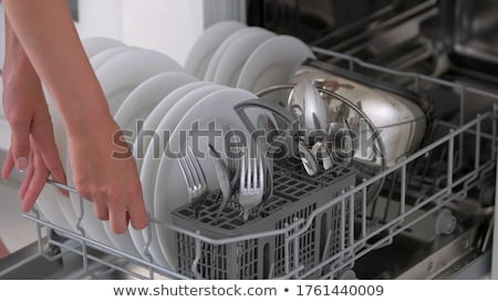 Woman's hand opening dishwasher with clean utensils Stock photo © vladacanon