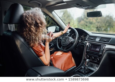 attractive blonde beauty using lipstick in a car stock photo © konradbak