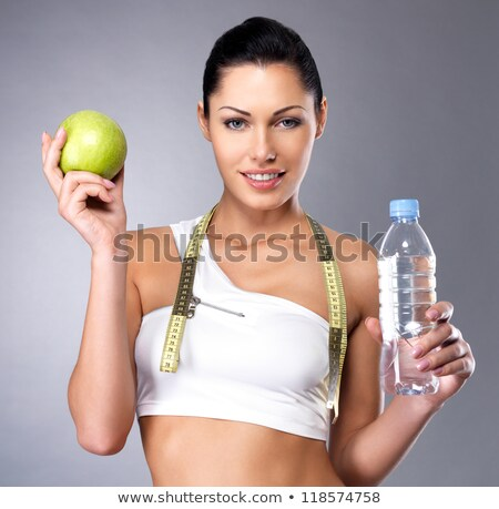 Stock photo: Sports woman holding an apple and bottle of water