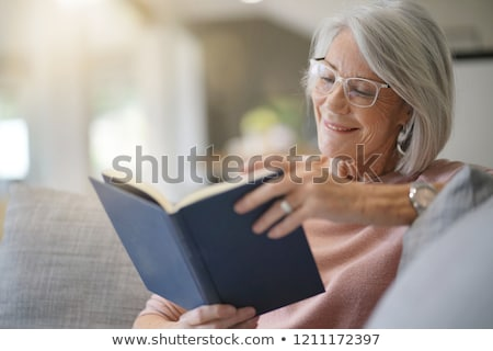 Portrait of a smiling senior woman reading a book sitting on a b Stock photo © FreeProd