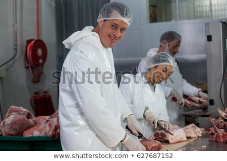 Female butcher cutting meat at meat factory Stock photo © wavebreak_media