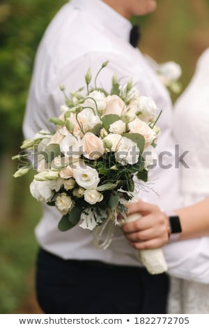 Blond woman with bouquet posing in a wedding dress. Close up Stock photo © dashapetrenko