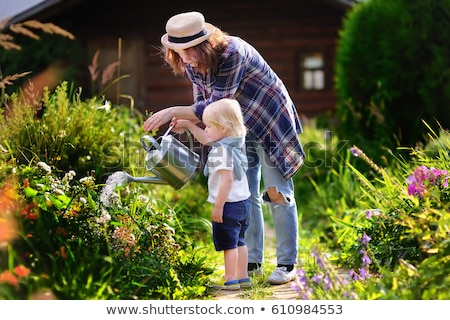 Cute little toddler boy watering plants with watering can in the garden. Adorable little child helpi stock photo © galitskaya