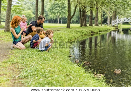 Families with children close to a waterscape with duck on it Stock photo © Lopolo