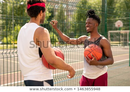 Two young multicultural basketball players interacting after game Stock photo © pressmaster
