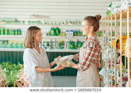 Young woman and her mature colleague in aprons looking at touchpad display Stock photo © pressmaster