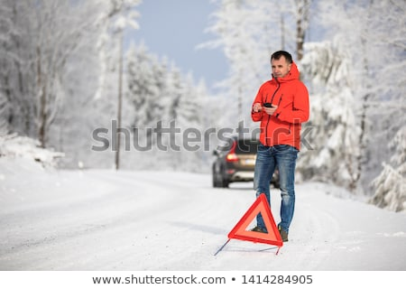 Handsome man setting up a warning triangle and calling for assistance Stock photo © lightpoet