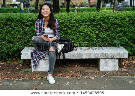 Asian relaxed woman sitting with crossed legs in park Stock photo © dash