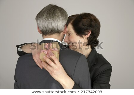 Affectionate woman with toothy smile and closed eyes embracing her senior father Stock photo © pressmaster