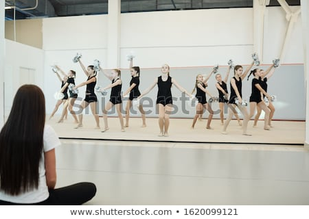 Cheerleaders dancing at dress rehearsal in front of coach Stock photo © pressmaster