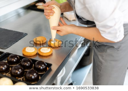 Pastry chef using icing bag to put creme on cake Stock photo © Kzenon