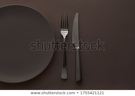 Empty plate and cutlery as mockup set on brown background, top tableware for chef table decor and me Stock photo © Anneleven