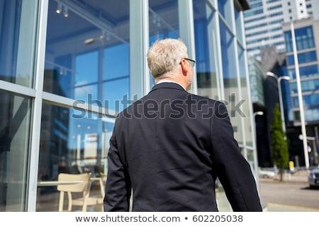 senior businessman walking along city street Stock photo © dolgachov