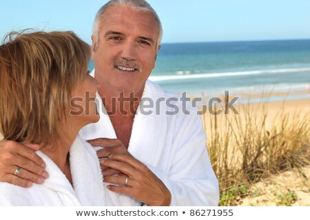 Mature woman gazing lovingly at her partner in the sand dunes Stock photo © photography33