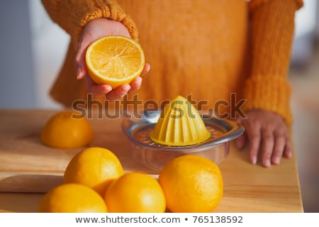a woman squeezes orange juice in kitchen stock photo © annakazimir