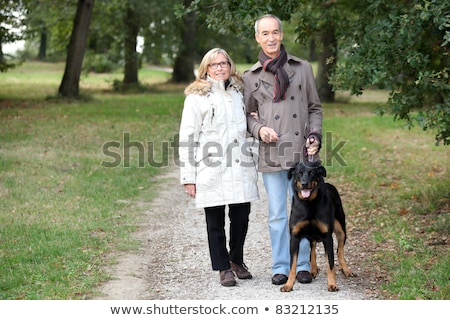 Stock photo: a 60 years old woman holding husband's arm in a park in autumn,  the man is keeping a dog on the lea