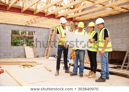 Construction Worker On Building Site Looking At House Plans Stock photo © HighwayStarz