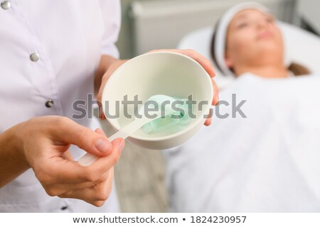 Beautician hands are mixing and applying clay facial mask  Stock photo © HASLOO
