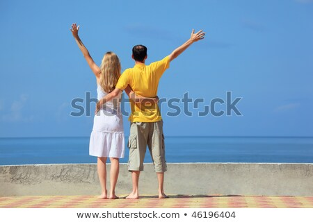 young man and beautiful woman on quay lifted hands upwards  Stock photo © Paha_L