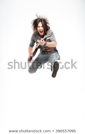 Stock photo: Excited joyful male guitarist with electric guitar shouting and jumping